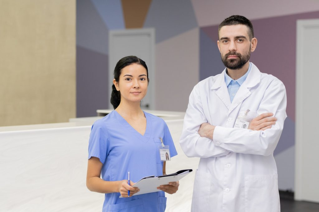 Pretty young assistant in blue uniform and confident dentist in whitecoat
